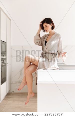 Portrait of sexual elegant woman with short dark hair wearing robe posing in kitchen sitting on table in sunny morning