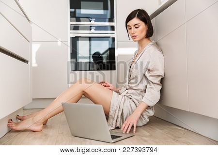 Caucasian gorgeous woman wearing robe sitting on floor in kitchen and working or communicating online via personal computer
