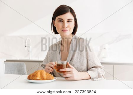 Image of attractive morning woman in robe having breakfast in hotel room and enjoying croissant with tea