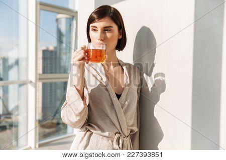 Gorgeous woman with short dark hair in robe drinking tea and enjoying sunny weather while standing near window in posh apartment