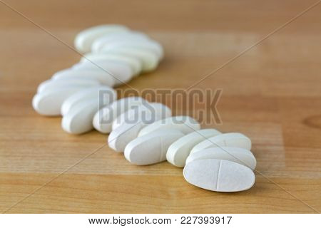 Oval Calcium Magnesium vitamin tablets to prevent osteoporosis, bone health formula on wooden background