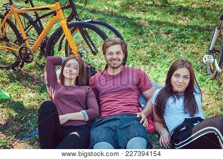 Group Of Friends Is Sitting On The Ground Relax And Talk Together After Biking In The Park. Friendsh