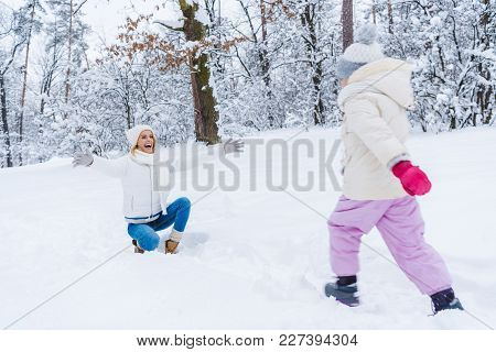 Happy Mother Kneeling With Open Arms And Little Daughter Walking In Snow In Winter Park