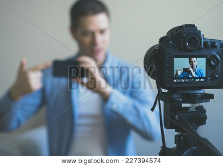 Man Making Video Blog About Mobile Phones. Focus On Camera.