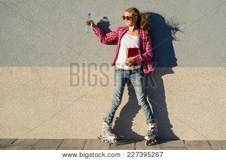 Girl Teenager For An Active Lifestyle. Poses On The Background Of The Wall Is Shod In The Quad Rolle