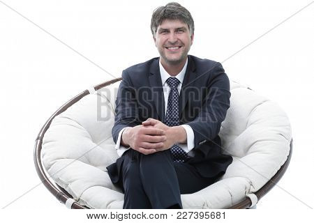 Successful businessman sits in a soft comfortable chair.