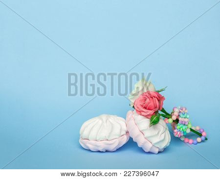 Rose Flower And Zephyr Marshmallows On Blue Pastel Color Background. Sweet Dessert With Marshmallows