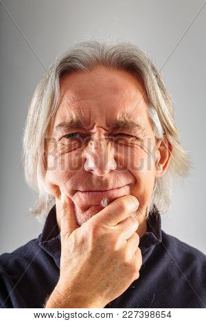 Studio Shot Of A Senior Man With Grey Background