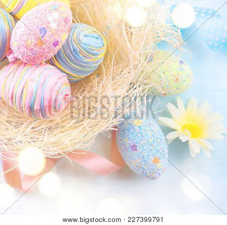 Easter colorful eggs background. Beautiful colorful eggs with decorations over blue wooden background, border design in pastel colors