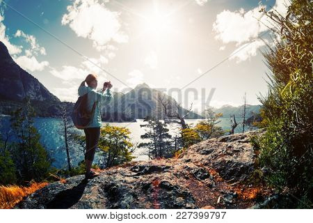 Woman hiker takes a pictures of a valley with lake and mountains. Patagonia, Argentina