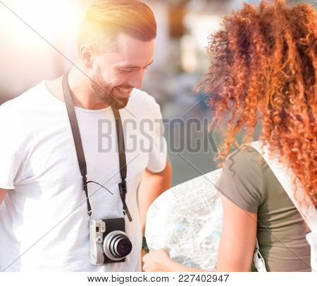 Young couple walking and looking at a guide while looking happy