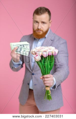 Handsome Bearded Man Holding Bouquet Of Tulips And Money In Hand On Pink Background. Womens Day. 8 M