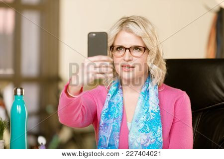 Pretty Professional Woman Communicating Or Taking Slefie With Smart Phone