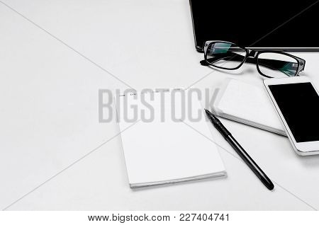 Workplace With Blank Tablet, Notepad And Pen, Smartphone And Glasses  On It To The Right, Office, Co