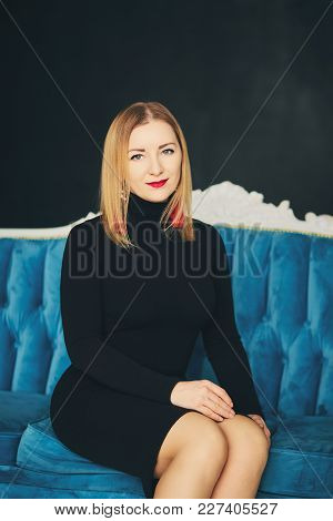 Young Attractive Woman In Black Dress Is Sitting And Smiling On Blue Sofa Indoors. Beautiful Lady In