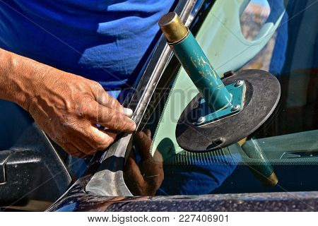 The Step Of Installing A Metal Clip In The Process Of Replacing A New Windshield On A Pickup.