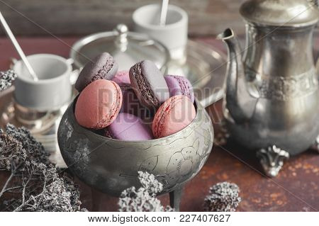 Freshly Baked Macaroons On Metal Plate With Small White Flowers And Tea Appliances Composition On Wo
