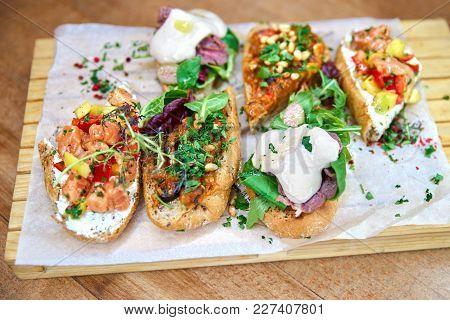 Board With Tasty Fresh Bruschettas On Table