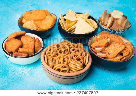 Salty snack including peanuts, potato chips and pretzels served as party food in bowls