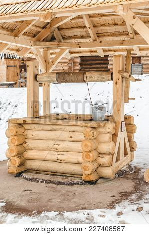 An Ancient Wooden Well Of Handwork With Bucket. Woodcraft, Village Traditions.