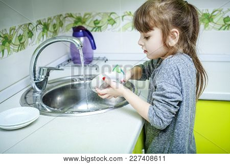 A Little Girl Stands On A Chair And Carefully Washes Dishes In The Kitchen.