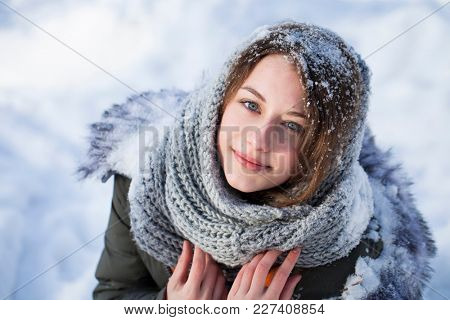 Winter Outdoor close up portrait of young beautiful girl wearing white knitted scarf. Model posing in street. Winter holidays concept.