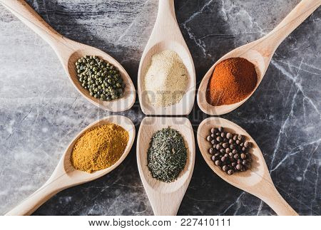 Six light wooden spoons with colorful spices on them. Aromatic seasoning. Cooking ingredients.