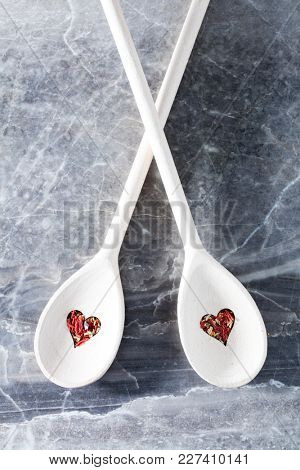 Two wooden spoons with heart-shaped holes and dry chili spice laying on a counter.