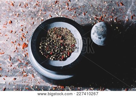 Mixed colorful grains of pepper in a mortar on a messy kitchen counter. Fresh seasoning.