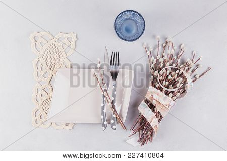 Easter Table Setting. Plate, Blue Glass, Cutlery, Lace Napkin And Pussy Willow Twigs On Light Stone