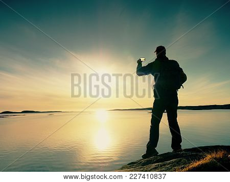 Tourist With Phone In Hand And Backpack Stand On A Rock. Hiker Looking Over Blue Sea And Taking Phot
