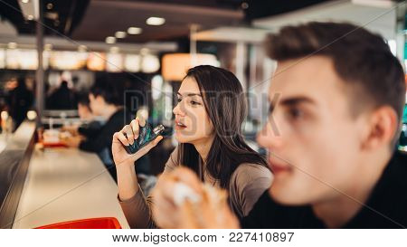 Young Woman Using Electronic Cigarette To Smoke In Public Places.smoke Restriction,smoking Ban.using