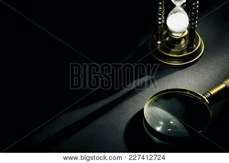 Old Vintage Hourglass With Magnifying Glass With Shadow On Dark Background With Free Space .
