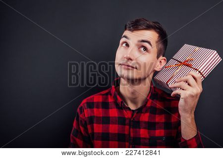 Young Handsome Man Shakes A Gift Box To Find Out What's In It