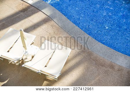 Beige sun beds by the pool. Closed umbrella to sunbathe in the sun