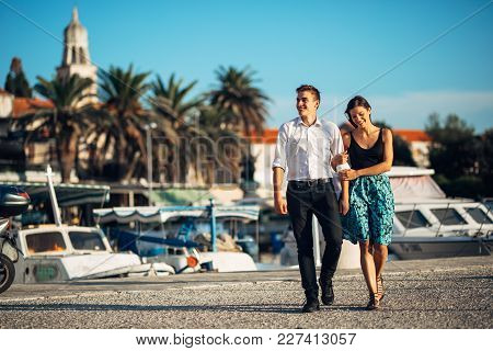 Young Couple Walking Along The Coastal Lane In Sunset.man Turning To See Another Woman,seeing Ex Gir