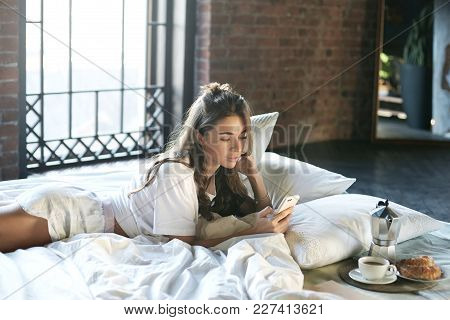 Lazy Pretty Woman Dressed In White T-shirt And Shorts Having Rest In Her Modern Bedroom With Large W