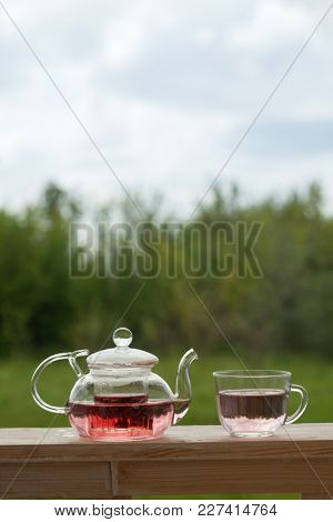 Teapot with fragrant herbal tea on a background of nature.