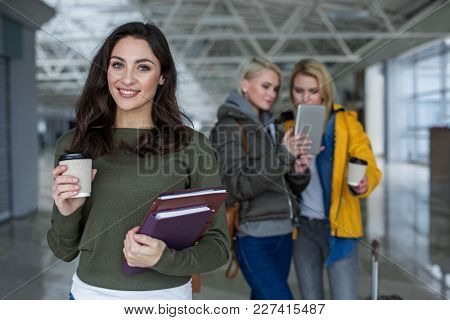 Waist Up Portrait Of Beautiful Lady With Happy Face Holding Cup Of Drink And Literature. Focus On He