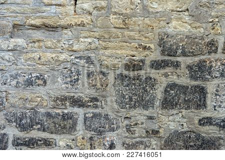 A Stone Wall Built Very High To Protect A Property