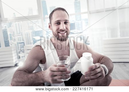 Additional Resources. Vigorous Pretty Cheerful Sportsman Taking Vitamins For Helping Organism And Lo