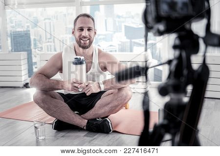 Water During Training. Jolly Positive Male Blogger Training While Smiling And Holding Bottle