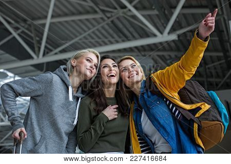 Low Angle Of Three Adults Waiting For Flight. They Are Smiling While One Woman Is Indicating With Fo