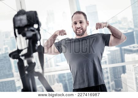 Fitness Blog. Vigorous Charming Male Blogger Showing Biceps While Sharing His Fitness Program And Us