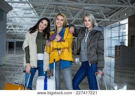 Portrait Of Content Friends Gathering For Flying Abroad On Weekend. They Are Standing At The Airport