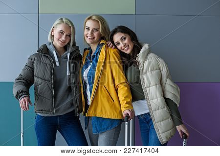 Portrait Of Joyous Ladies Gathering Together With Bags In Hands. They Are Standing In Embrace