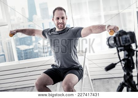 Sport Activities. Handsome Bearded Male Blogger Using Equipment For Working Out And Posing On Chair