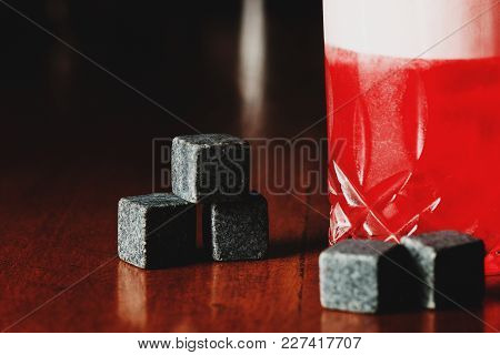 Red Cool Alcohol. Cooling Stones On Wood.