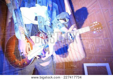 Performing, Show, Talent Concept. There Is Male Musician That Is Holding Rock Guitar, His Unclear Fi