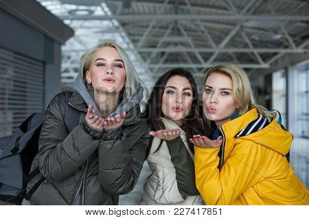 See You Soon. Waist Up Portrait Of Satisfied Attractive Girls Giving Air Kiss In The Airport Hall Be